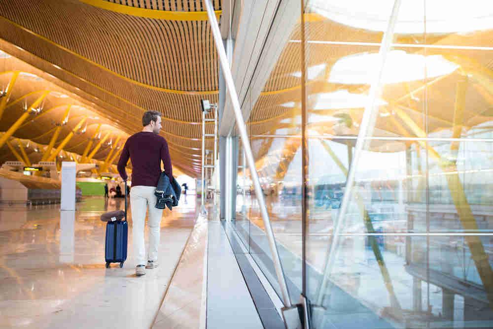 homme aéroport voyage marche avec savalise